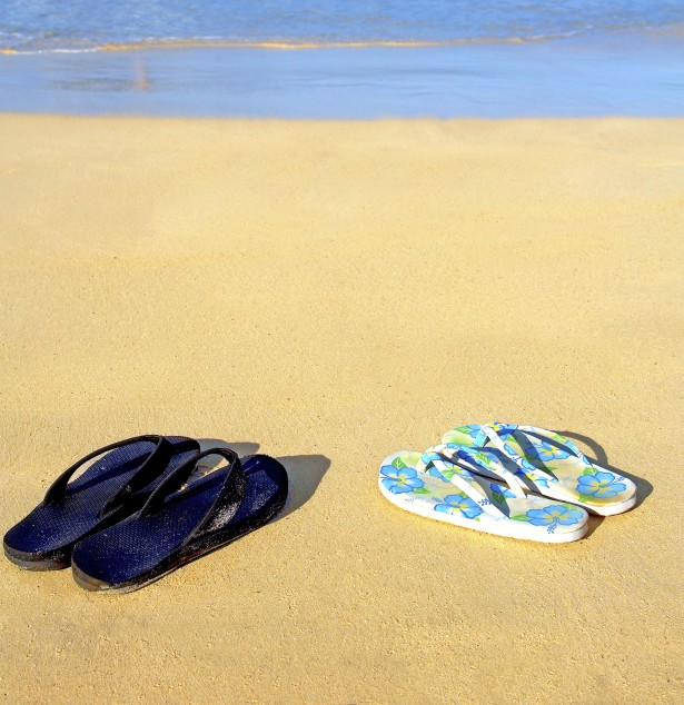 This is a shot of two pairs of sandals on the beach with a woman in the water in the background.
