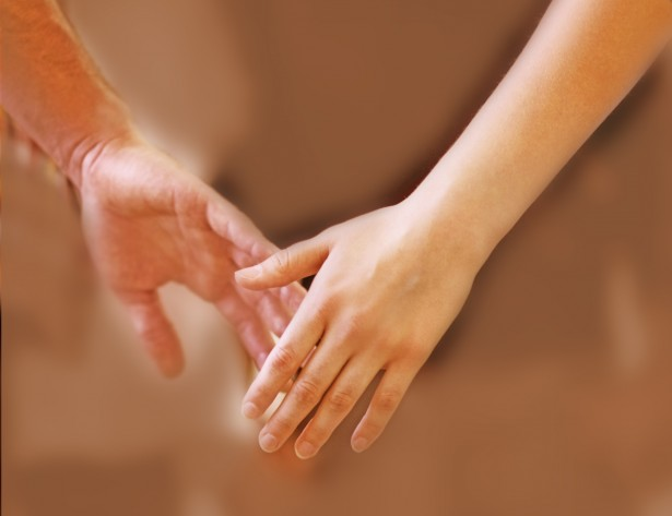 A closeup cropped shot of young people holding hands during a group therapy session