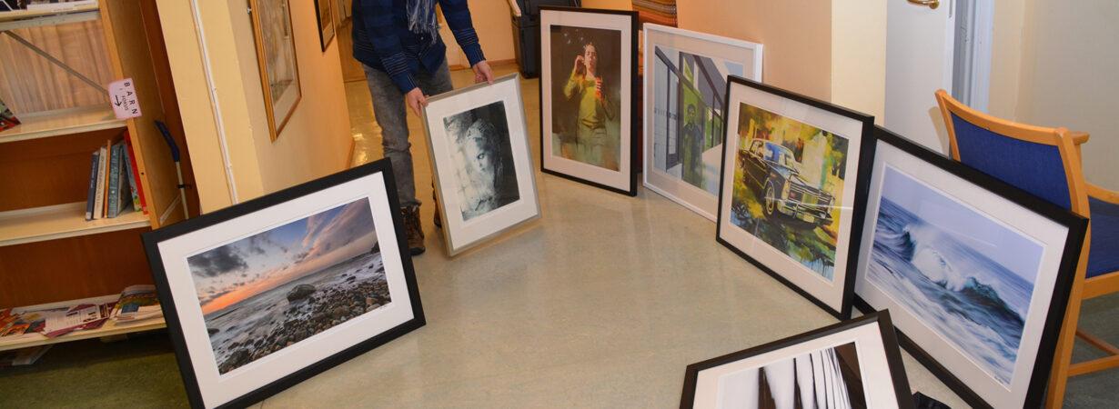Helge Harila viser fram sju nye bilder som er kjøpt inn til artoteket.